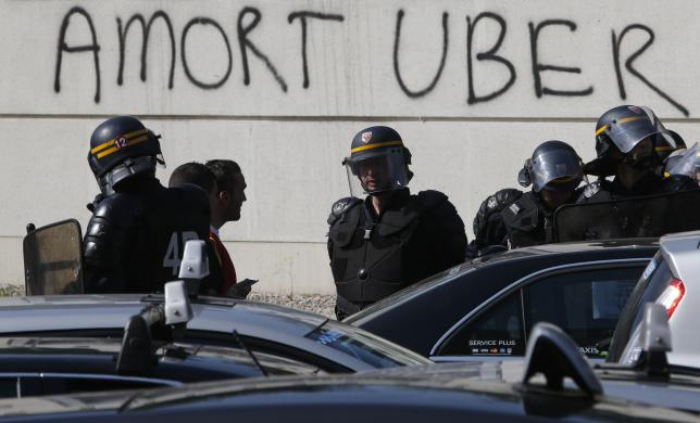French riot police secure the Porte Maillot during a demonstration by French taxi drivers, who are on strike, to block the traffic on the Paris ring road during a national protest against car-sharing service Uber, in Paris