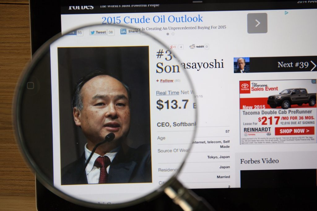 Photo of Forbes article page about Masayoshi Son on a ipad monitor screen through a magnifying glass