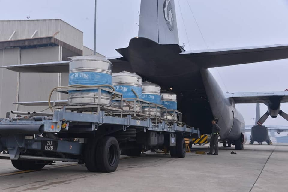 Four tanks of salt and water mixture are loaded into RMAF's Lockheed C-130 Hercules transporter.